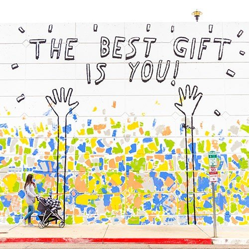 Mother with stroller walking. Wall says the best gift is you